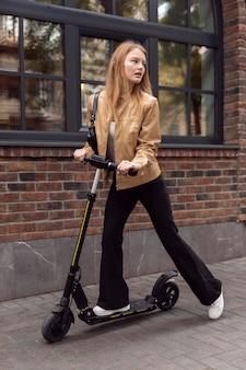 Kobieta jedzie skuterem elektrycznym na zewnątrz w mieście