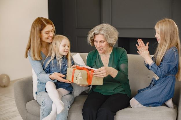 Kobieta, jej matka i córka siedzą na kanapie. dziewczyna trzyma pudełko z prezentem i daje je swojej babci.
