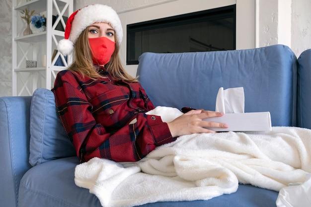 Kobieta jest chora na boże narodzenie. młoda blondynka w czerwonej koszuli i świątecznej czapce w ochronnej masce medycznej leży na kanapie z serwetkami