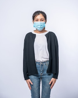 Kobieta jest chora stojąca w masce. załóż czarny płaszcz i dżinsy.