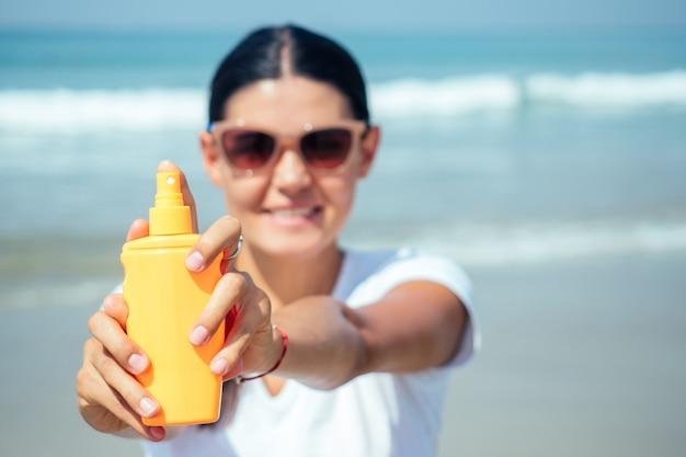 Kobieta jest chroniona przed promieniami ultrafioletowymi za pomocą kremu przeciwsłonecznego na plaży