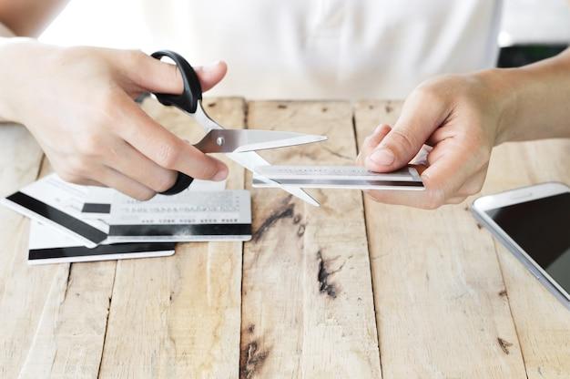 Kobieta jest cięcie karty kredytowej nożyczkami nad innymi kartami kredytowymi na stole