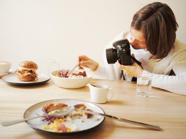 Kobieta jest fotografowaniem restauracji jedzeniem