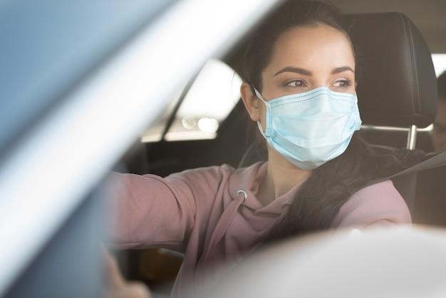 Kobieta jest ubranym chirurg maskę w samochodzie
