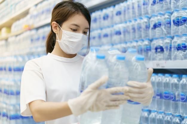 Kobieta jest ubranym chirurgicznie maskę i rękawiczki kupuje wodę pitną w supermarkecie. panika po pandemii koronawirusa.