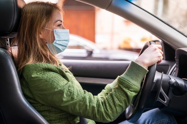 Kobieta jest ubranym chirurgicznie twarzy maskę w samochodzie