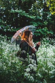 Kobieta jest ubranym czarnego kurtki mienia parasol obok zielonych rośliien podczas dnia