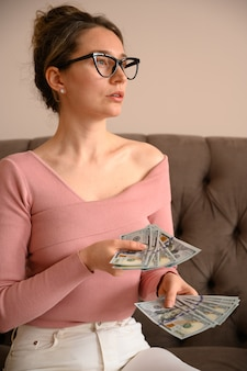Kobieta jest ubranym czarnych szkła myśleć pieniądze