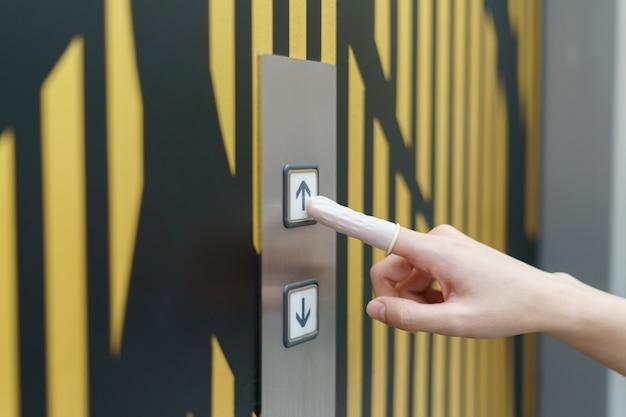 Kobieta jest ubranym gumę dla palca naciska up guzika winda guzik w budynku. unieważnić bezpośredni kontakt podczas wybuchu covid-19.