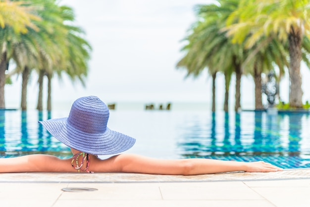 Kobieta jest ubranym kapelusz w hotelowym basenu kurorcie