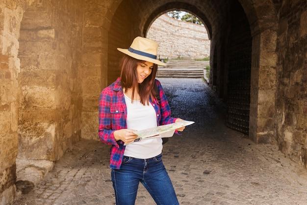 Kobieta jest ubranym kapeluszowego patrzeć kierunek w mapie