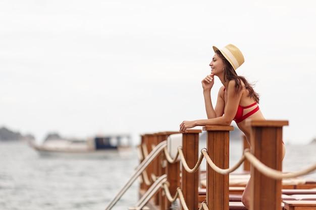 Kobieta jest ubranym kapeluszowego patrzejący morze