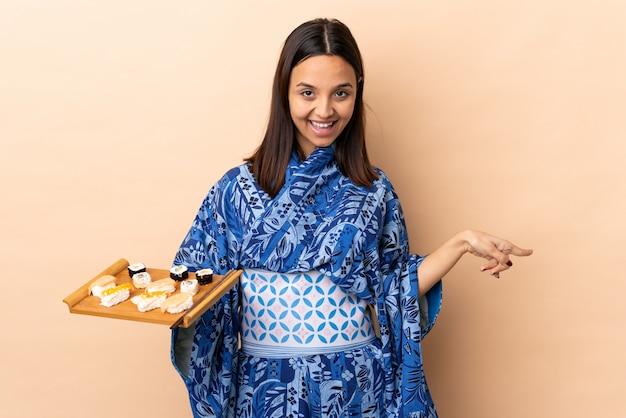 Kobieta jest ubranym kimono i trzyma suszi nad odosobnionym wskazuje palcem laterals i szczęśliwa