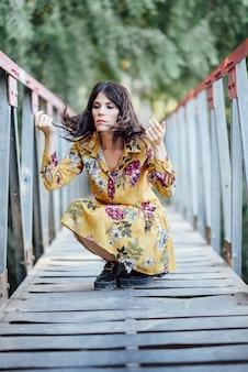 Kobieta jest ubranym kwitnącą suknię wycieczkuje w wsi