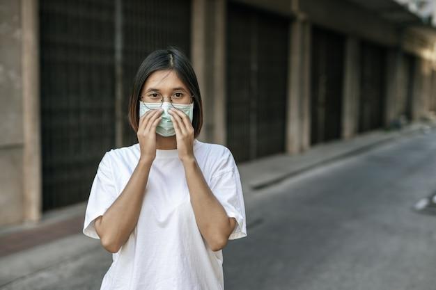 Kobieta jest ubranym maskę na ulicie.