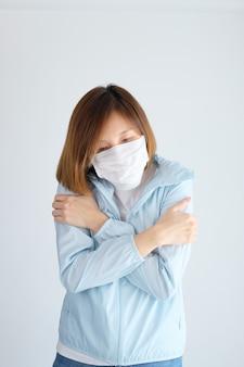 Kobieta jest ubranym maskę ochronną i jest zimna