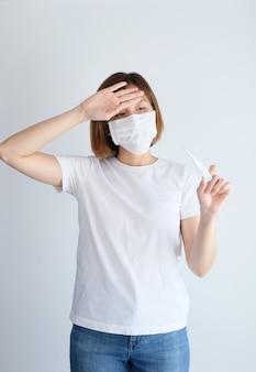 Kobieta jest ubranym maskę ochronną patrzeje termometr