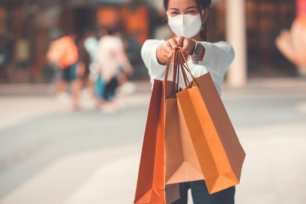 Kobieta jest ubranym maskę ochronną podczas gdy trzymający papierowe torby