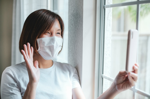 Kobieta jest ubranym maskę ochronną robi rozmowie wideo
