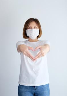 Kobieta jest ubranym maskę ochronną robi sercu z rękami
