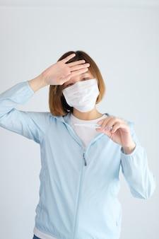 Kobieta jest ubranym maskę ochronną używać termometr