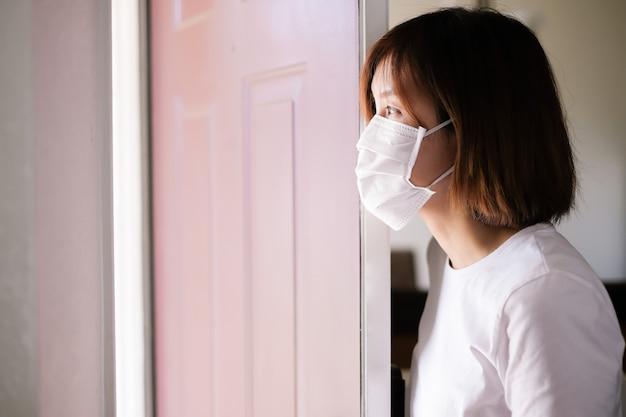 Kobieta jest ubranym maskę ochronną w domu