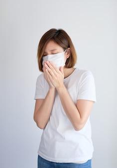 Kobieta jest ubranym maskę ochronną zakrywającą jej usta