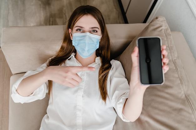 Kobieta jest ubranym maskę pokazuje puste miejsce kopii telefonu telefonu ekran w domu na kanapie