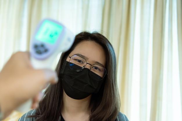 Kobieta jest ubranym maskową ochrony grypę z thermoscan