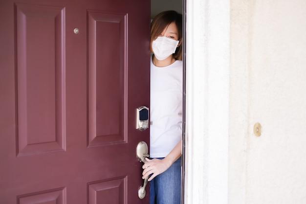 Kobieta jest ubranym ochronną maskę chuje za domowym drzwi