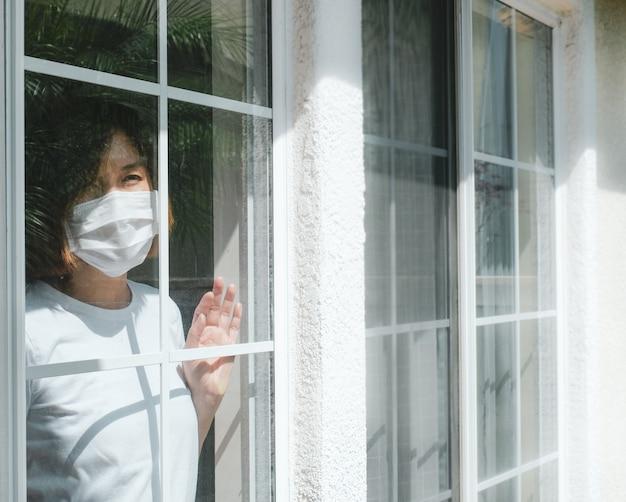 Kobieta jest ubranym ochronną maskę patrzeje przez okno