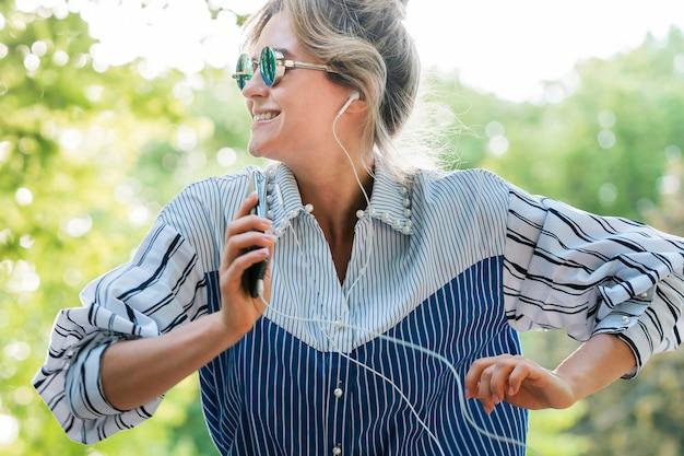 Kobieta jest ubranym okulary przeciwsłonecznych i słucha muzyczny frontowy widok