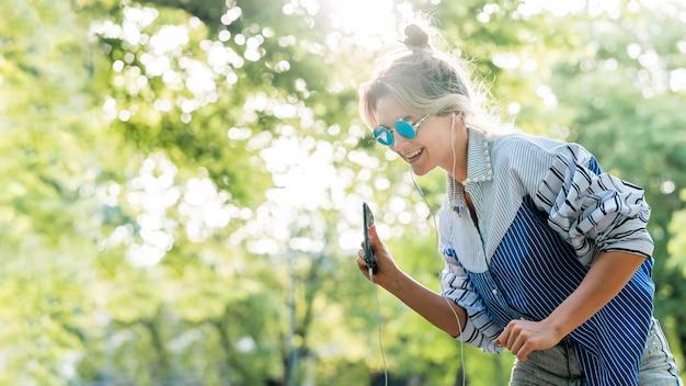 Kobieta jest ubranym okulary przeciwsłonecznych i słucha muzyka