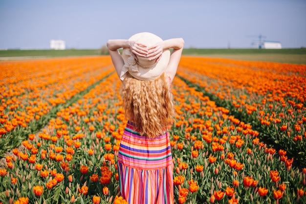 Kobieta jest ubranym pasiastą smokingową pozycję z powrotem na kolorowym tulipanu polu z długim czerwonym włosy.