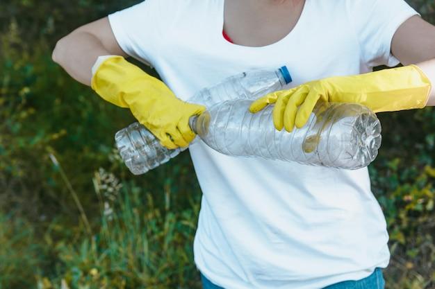 Kobieta jest ubranym rękawiczki trzyma przetwarzalne plastikowe butelki - plastikowy zanieczyszczenia pojęcie