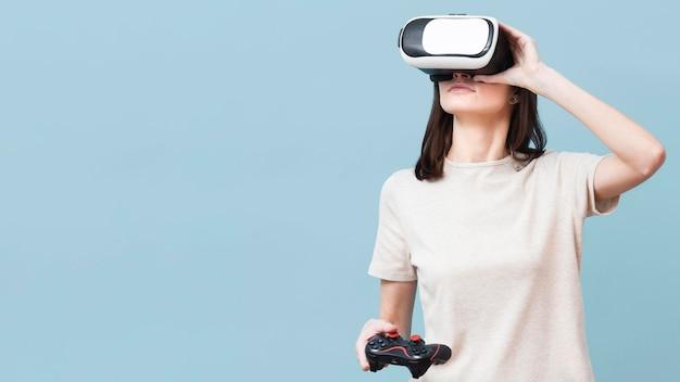 Kobieta jest ubranym słuchawki wirtualnej rzeczywistości i trzyma pilot do tv