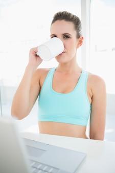 Kobieta jest ubranym sportswear pije kawę