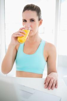 Kobieta jest ubranym sportswear pije sok pomarańczowego