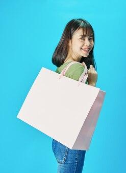 Kobieta jest ubranym zielone koszula trzyma torba na zakupy