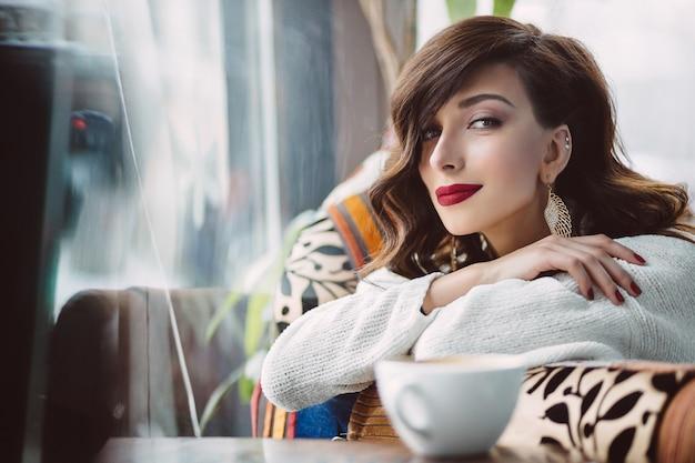 Kobieta jest usytuowanym na krześle w kawiarni