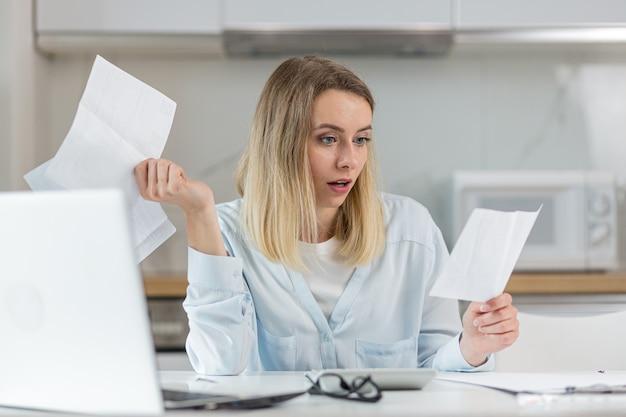 Kobieta jest wyczerpana i sfrustrowana dokumentami przedsiębiorstwa lub budżetu rodzinnego w domu