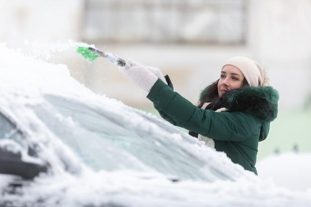 Kobieta jest za niska, by odśnieżać dach swojego samochodu, po tym, jak duże opady śniegu pozostawiły pojazdy przykryte białym pokrowcem.