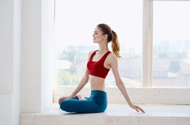 Kobieta jest zaangażowana w medytacyjną asanę jogi w pobliżu okna