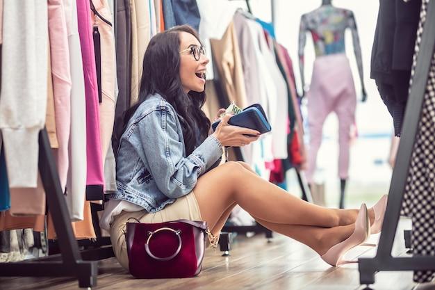 Kobieta jest zachwycona odkryciem banknotu o wartości stu euro w torebce, gdy siedzi na podłodze w sklepie z modą.