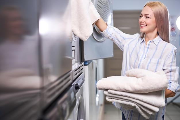Kobieta jest zadowolona z czystych ręczników z pralki, stoi uśmiechnięta, widok z boku
