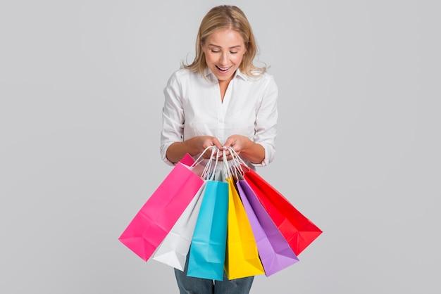 Kobieta jest zadowolona z wielu toreb na zakupy, które trzyma