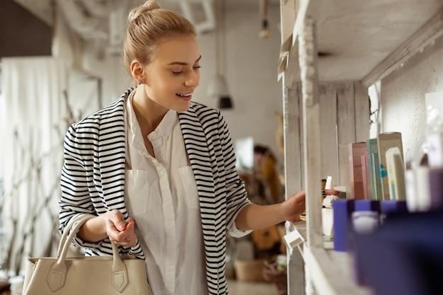Kobieta jest zajęta. podekscytowana młoda kobieta w czarno-białym stroju obserwująca półki z kosmetykami w salonie kosmetycznym
