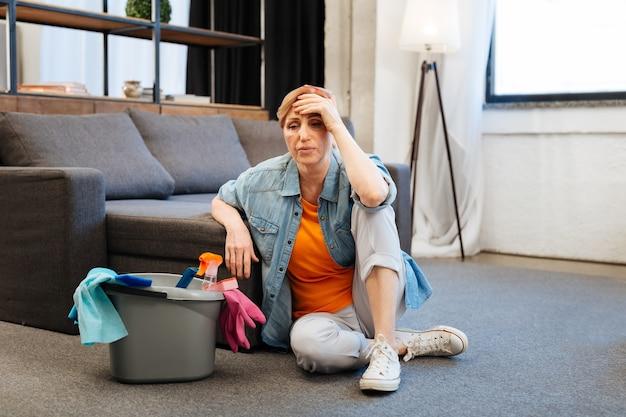 Kobieta jest zaniepokojona. zmęczona przygnębiona kobieta czuje się źle po intensywnym sprzątaniu w przestronnym mieszkaniu