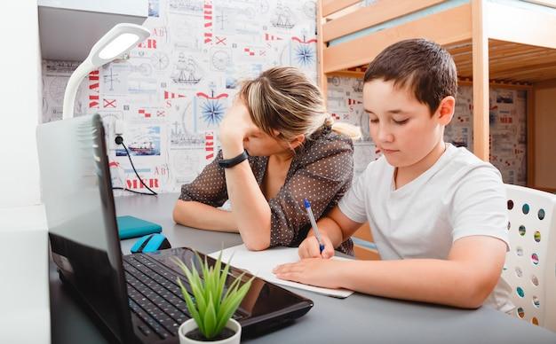 Kobieta jest zdenerwowana, ponieważ musi pracować w domu z dzieckiem. nauczanie domowe, kształcenie na odległość, edukacja dzieci online. praca zdalna, praca na zlecenie.