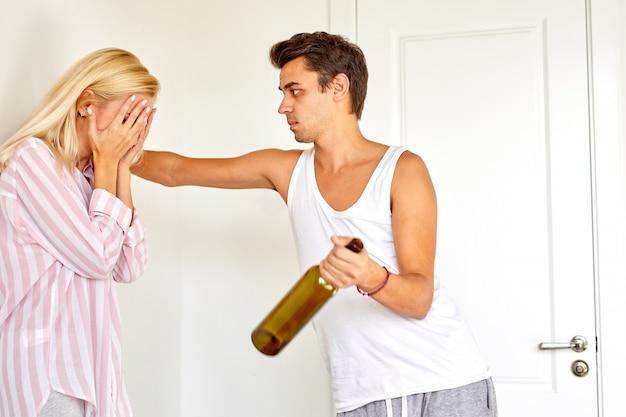 Kobieta jest zdenerwowana swoim pijanym mężem w domu, blond żona obwinia męża alkoholika